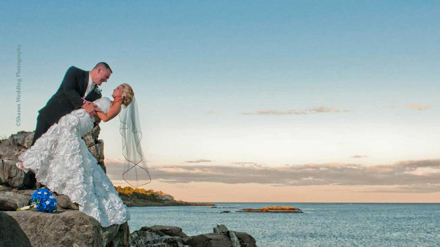 Bride and groom pose on the point after their oceanfront wedding.