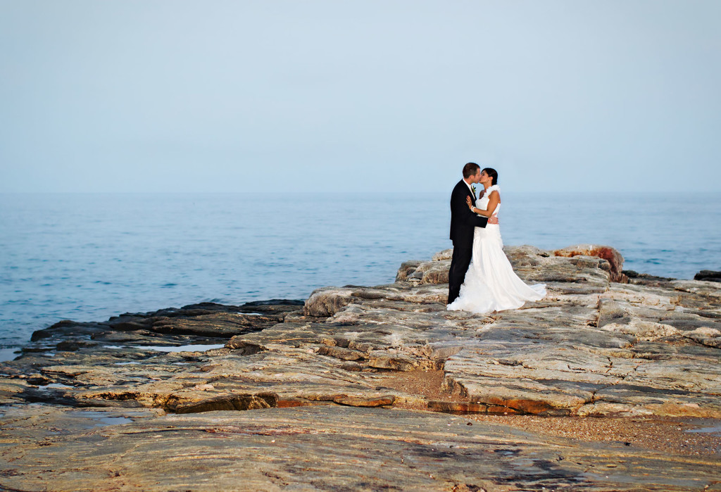Couple kissing on rocks of Madison beach Hotel